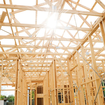 The sun shining through the skeleton of a new home built using lumber and stick-frame construction